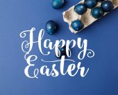 Fotografie top view of blue painted easter eggs and egg tray with happy easter lettering on blue surface