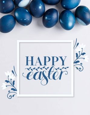 top view of blue painted easter eggs with happy easter lettering on white