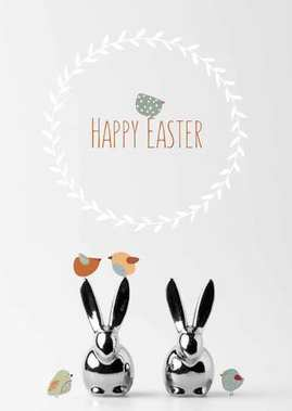 two statuettes of easter bunnies with drawn birds and happy easter lettering on white
