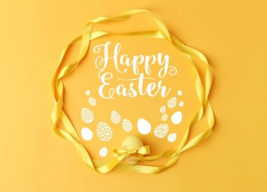 top view of yellow painted easter egg with ribbons on yellow with happy easter lettering