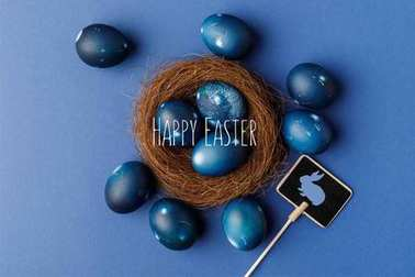 top view of blue painted easter eggs with happy easter lettering in decorative nest on blue surface