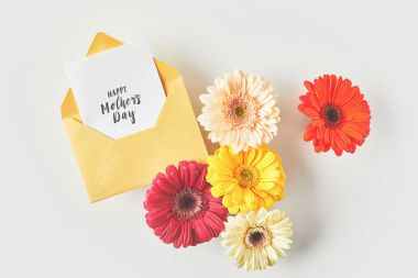 Top view of happy mothers day greeting card and beautiful gerbera flowers on grey stock vector