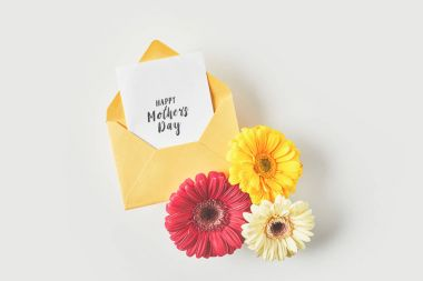 top view of happy mothers day greeting card in envelope and beautiful gerbera flowers on grey