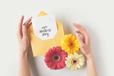 cropped shot of human hands with envelope, gerbera flowers and happy mothers day greeting card on grey