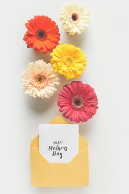 Top view of beautiful tender gerbera flowers and envelope with happy mothers day greeting card on grey stock vector