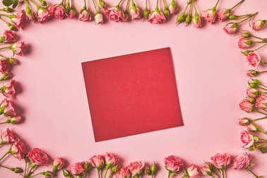 top view of frame made from beautiful pink roses and blank card on pink