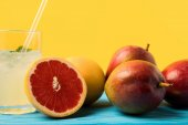close-up view of fresh ripe grapefruits and mangoes and glass with cold summer drink on yellow