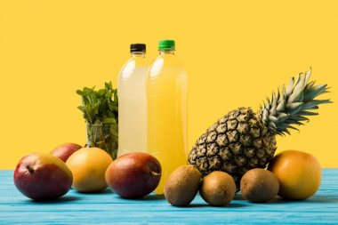 fruity drinks in plastic bottles and fresh ripe tropical fruits on turquoise wooden table top