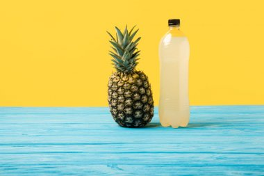 close-up view of fresh juice in plastic bottle and ripe pineapple on yellow