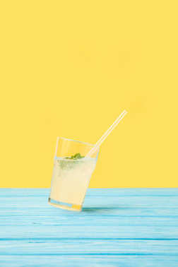 glass with fresh cold summer cocktail and drinking straw on yellow