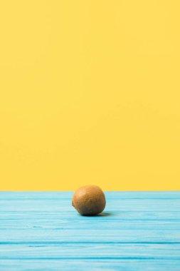 single fresh ripe kiwi fruit on turquoise wooden table top