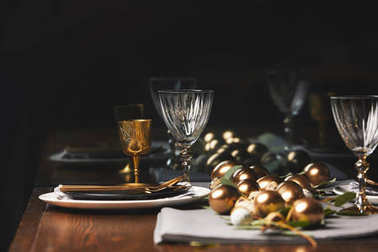 glasses, plates and easter eggs on wooden table in restaurant
