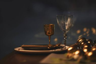 glasses with plates and golden easter eggs on table