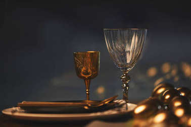 golden easter eggs and glasses with plates on festive table