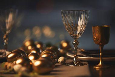 golden easter eggs and glasses on festive table
