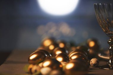 close up of golden easter eggs and glass on table