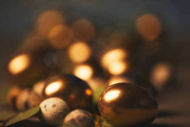 close up of easter golden eggs and quail eggs with leaves on table