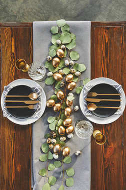 top view of easter golden eggs, plates and utensil on festive table in restaurant