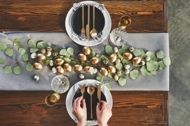 cropped image of waiter decorating easter table in restaurant