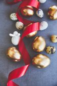 Fotografie top view of golden easter eggs and quail eggs on tablecloth