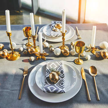 easter eggs and candles on festive table with sunlight