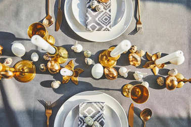 top view of easter decorated table with golden eggs