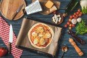vista superiore della pizza cruda il vassoio sul tavolo in cucina
