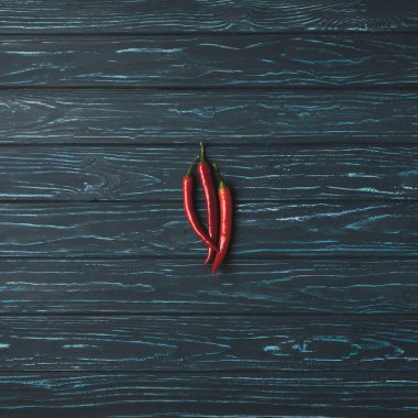 top view of three chili peppers on wooden table
