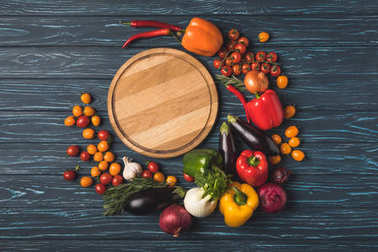 top view of ripe organic vegetables around wooden board on surface