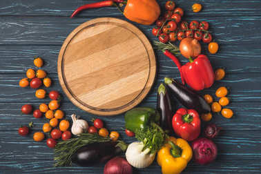 top view of ripe organic vegetables around wooden board on tabletop