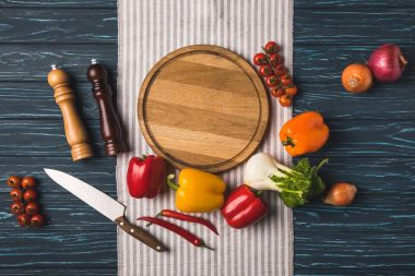 top view of ripe organic vegetables and cutting board on wooden table