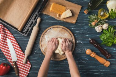 cropped image of woman kneading dough for pizza