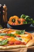 Fotografie zblízka chutná chutné pizzy s cherry rajčaty a bazalkou