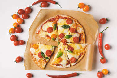 top view of appetizing tasty homemade pizza on white table