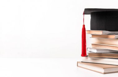 Cropped view of quare academic cap on stack of different books isolated on white