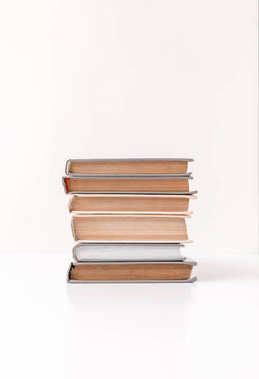 Front view of stack of different books isolated on white