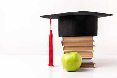 Close up view of apple near pile of books with academic cap on top isolated on white