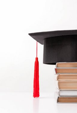 Cropped view of academic cap on pile of books isolated on white