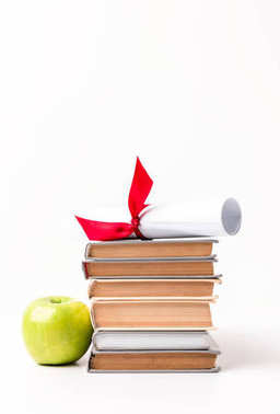Diploma on pile of books and apple isolated on white