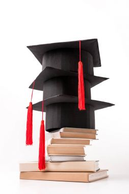 Square academic hats on pile of books isolated on white