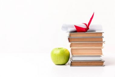 Apple near pile of books with diploma on top isolated on white