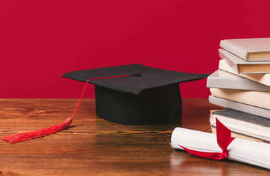 Cropped image of pile of books with diploma and academic cap on red