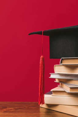 Cropped image of academic cap on pile of books on red