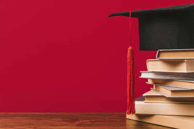 Cropped view of stack of books with academic cap on red