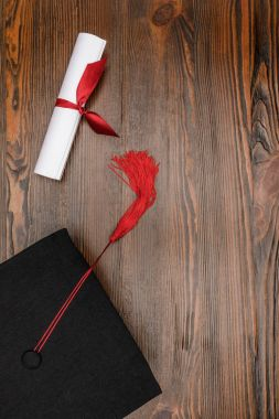 Top view of diploma and square academic hat on wood background