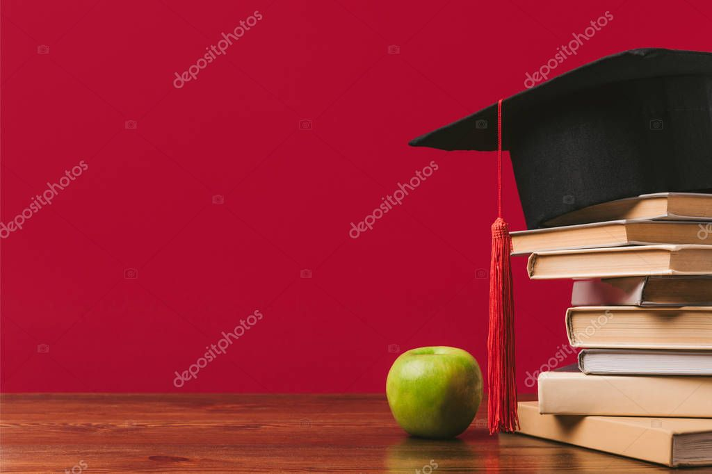 Cropped view of pile of books with academic cap on top and apple on red stock vector