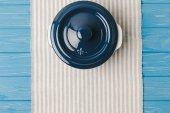 Fotografie Draufsicht der Pfanne auf Serviette auf blauen Holztisch