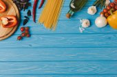 Fotografie top view of ingredients for cooking pasta on blue surface