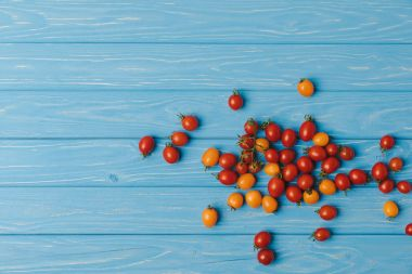 top view of red and orange cherry tomatoes on blue table