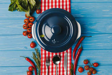 top view of blue pan and vegetables on blue table